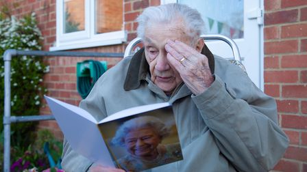 Arthur Squires salutes The Queen as he reads his 100th birthday card.