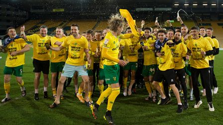 Norwich City players and backroom staff celebrate promotion back to the Premier League after defeat to Bournemouth