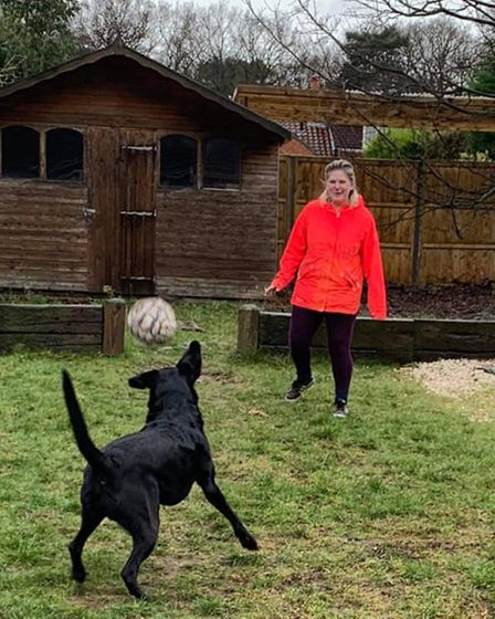 Norwich pet carer Tracy Eaton playing football with a dogat her home