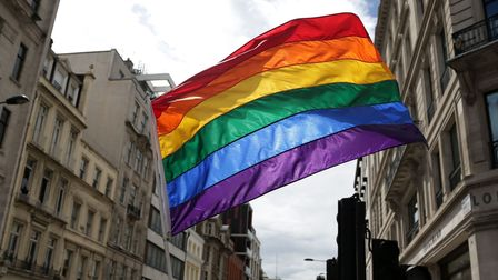 A rainbow flag is held aloft as the Pride in London parade makes its way through the streets of cent