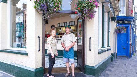 Paul and Simone stand smiling in the door way of Fish 'n' Fritz. Hanging baskets of flowers hang either side of the door.