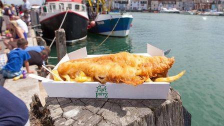 A cardboard carton of fish and chips sits on a post in front of the harbour. Boats can be seen in the background.
