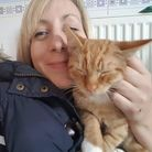 Charlie Gill, who is taking part in a skydive for charity, stroking a ginger cat