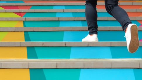 Lower part of teenage girl in casual shoe walking up outdoor colorful stair,teenage lifestyle succes