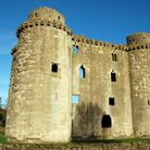 Nunney Castle stands against a blue sky. It's weathered stone is imposing.