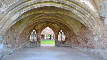 A cloister of red brick and weathered stone leads through an arch to a grassy courtyard.