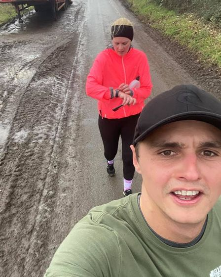 Two people in running gear on a muddy road, one in front of the other