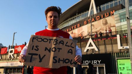 An Arsenal fan protests against the proposed European Super League