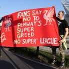 Liverpool fans hold up a protest banner against the European Super League outside Elland Road on April 19, 2021 in Leeds