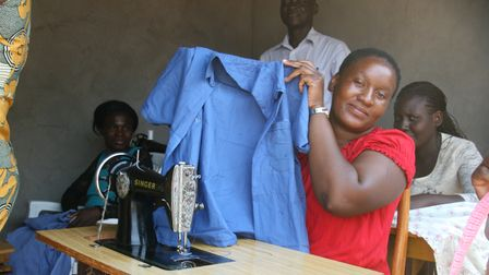 A woman in Zambia showing off her newly refurbished sewing machine fromTools with a Mission