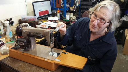One of Ipswich-based charity's volunteers giving a sewing machine a drop of lubrication to finish its refurbishment