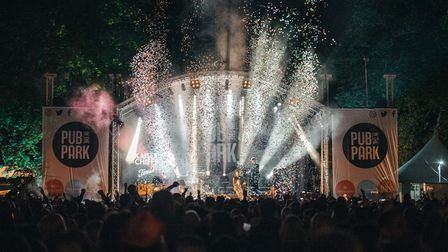 Confetti shoots across a stage as a band play in front of a crowd at night
