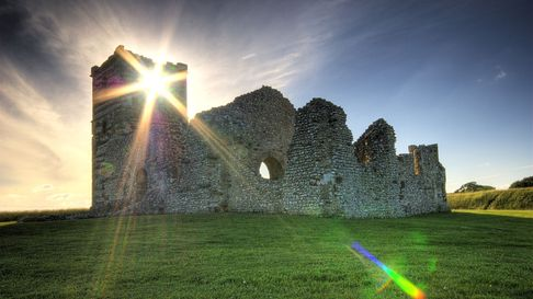The ruined Knowlton Church stand with the sun blazing behind its weathered stone. The church sits on an open field of grass.
