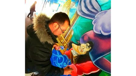 Mark Tanti - also known as Demograffix - adding the final details to the Peter Pan underpass mural in Stevenage