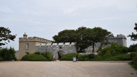 The entrance to Portland Castle can be seen. Trees rise from behind the walls.