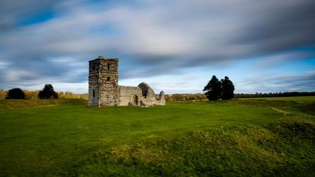 Knowlton Church sits in the centre of a round grassy ridge on a cloudy day.
