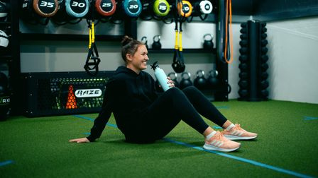 A happy girl relaxes in the Training Shed, a gym in st Ives, after a workout