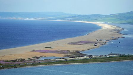 Chesil beach curves round to meet the road to Portland. You can see buildings along the road too.