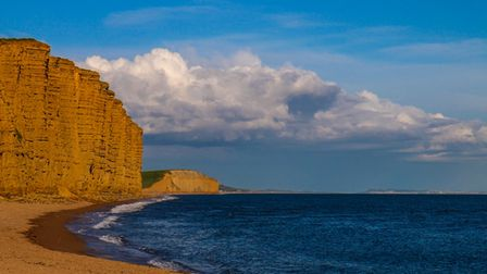 The distinct red rock of West Bay's cliff stand imposingly over the sea.