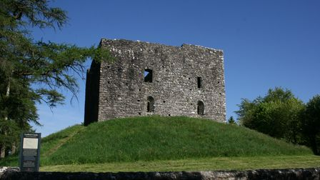 Atop a grassy mound, sits the square and solid ruin of Lydford Castle against a clear blue sky.
