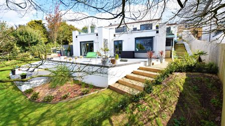 Exterior of white rendered villa-style house in Redcliffe Bay Portishead with terrace and steps down to lawned garden.