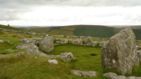 A collection of large stones are partially buried in the ground, they make a long room shape