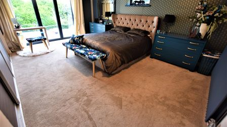 Large master bedroom suite in the house in Redcliffe Bay Portishead with brown carpet and double bed with bi-folding doors