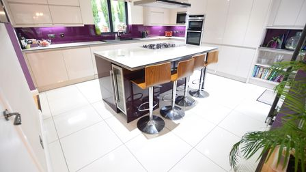 Modern kitchen with white gloss units with purple walls, island with breakfast bar and white floor tiles