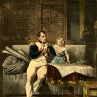 Napoleon, surrounded by books in his office, takes a break from reading to discuss military matter with a small child