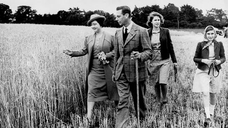File photo dated 30/09/1942 of King George VI and Queen Elizabeth walking in a field with their daug