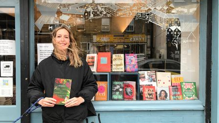 Jo Heygate, Bookshop Manager at Pages of Hackney holds up the book Antiemetic for Homesickness by Romalyn Ante.