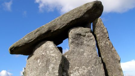 Five tall standing stones hold a huge slab up in a sloping manner.