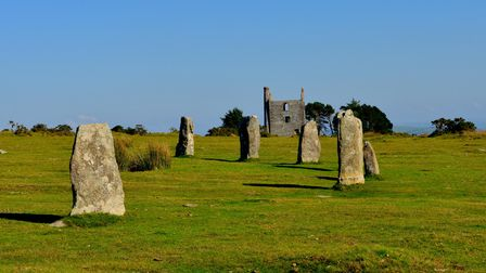 Tall standing stones make up a semi circle. In the distance a ruined engine house for a mine can be seen