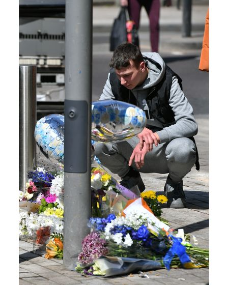 People place flowers at the scene