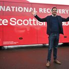 Scottish Labour leader Anas Sarwar poses in front of his party's election bus, in Glasgow