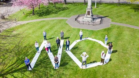 Protesters against the loss of free parking in Stevenage Old Town High Street stand on the Bowling Green, spelling out 'no'