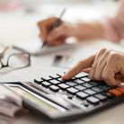 Pension calculation concept, old hands counting finances on a home calculator ,