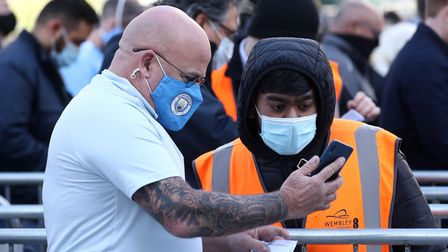A Manchester City fan shows a Covid-19 test result to a steward outside the stadium ahead of the Car