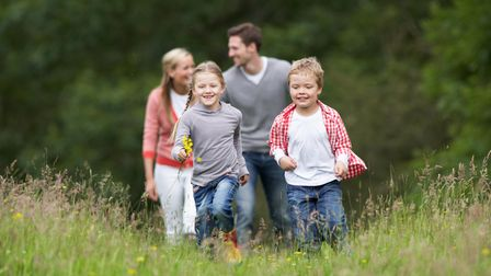 Family On Walk In Countryside, Walking Towards Camera And Smiling