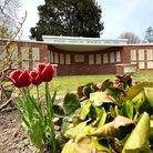 A brick building with a white canopy. In front of it, a lawn and red flowers