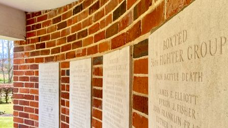 A brick wall with stone panels bearing names