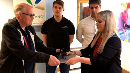 Ken Frankland receiving a laptop from The Accountancy Practice with Adam Froggett, David Froggett and Luci Shears.
