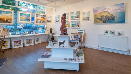A gallery with lots of colourful paintings inside. In the middle, a brown sculpture of a nude woman