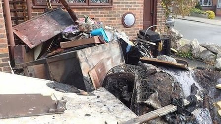 A wooden gazebo with a hot tub destroyed by fire