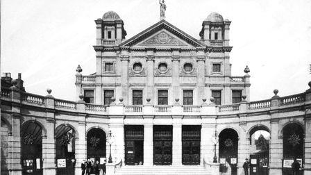 Small groups of people stand outside a grand building.