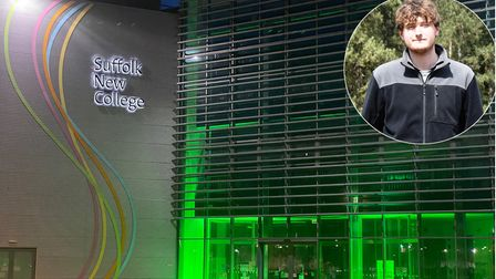 Suffolk New College lit up green and boy with brown hair looking directly at camera