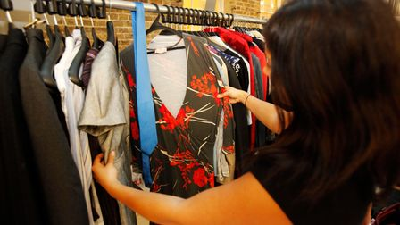 Civil Servant Nadine Smith looks at a dress and a tie donated by Prime Minister Gordon Brown and his