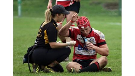 Fitness woman treating rugby player