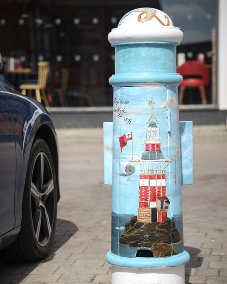 A light blue bollard with a lighthouse in the centre.
