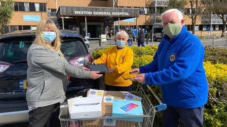 Cheddar Lions President Keith with Lions Lyn andSylvia presenting the devicesto Maria at Weston General's car park.